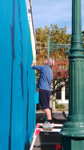 Artist David Higgins completing the top coat of his wall-canvas in Timor Walk. picture by Jenny Fawcett